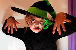 Small girl wearing Hallowe'en costume with face painted UK