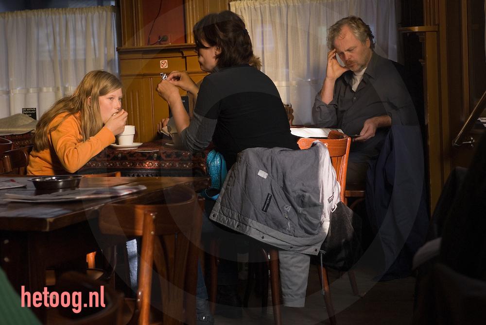 meisje drinkt chocolademelk/eet slagroom in cafe het bolwerk met (vermoedelijk) haar ouders...Enschede.