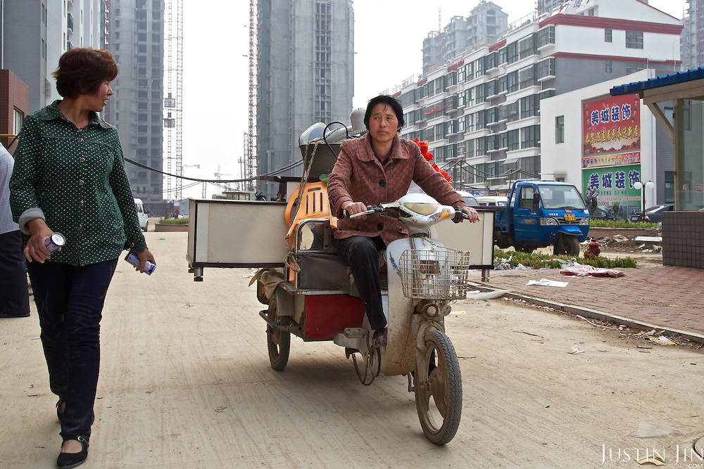 Chen Hua, 50, moves out of a village accommodation for her new urban home in the northeastern China.<br /> <br /> Her former village house was bulldozed by the government three years ago to make way for high-rise development. <br /> <br /> In the four years between her rural home being razed and the completion of her new city apartment, she and her family lived in temporary village housing such as this one. <br /> <br /> China is pushing ahead with a dramatic, history-making plan to move 100 million rural residents into towns and cities over the next six years &mdash; but without a clear idea of how to pay for the gargantuan undertaking or whether the farmers involved want to move.<br /> <br /> Moving farmers to urban areas is touted as a way of changing China&rsquo;s economic structure, with growth based on domestic demand for products instead of exporting them. In theory, new urbanites mean vast new opportunities for construction firms, public transportation, utilities and appliance makers, and a break from the cycle of farmers consuming only what they produce.<br /> <br /> Urbanization has already proven to be one of the most wrenching changes in China&rsquo;s 35 years of economic reforms. Land disputes rising from urbanization account for tens of thousands of protests each year.