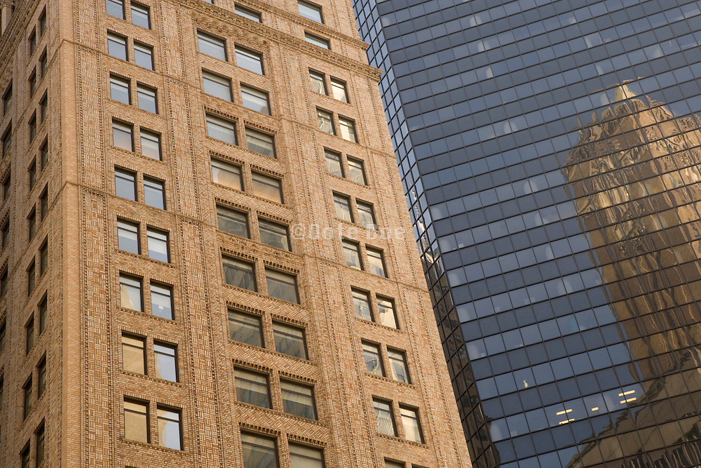 old building reflecting in a modern glass facade building