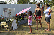 """East Meadow, New York, U.S. 11th September 2013. A young girl and family look at the Battlefield Cross display at the Global War on Terror """"Wall of Remembrance"""" a traveling memorial on display in New York for the first time, at Eisenhower Park on the 12th Anniversary of the terrorist attacks of 9/11. The unique 94 feet long by 6 feet high wall has, on one side, almost 11,000 names of those lost on September 11, 2001, along with heroes and veterans who lost their lives defending freedom of Americans over past 30 years. On the wall's other side is a timeline, with photos, covering 1983 to present day."""