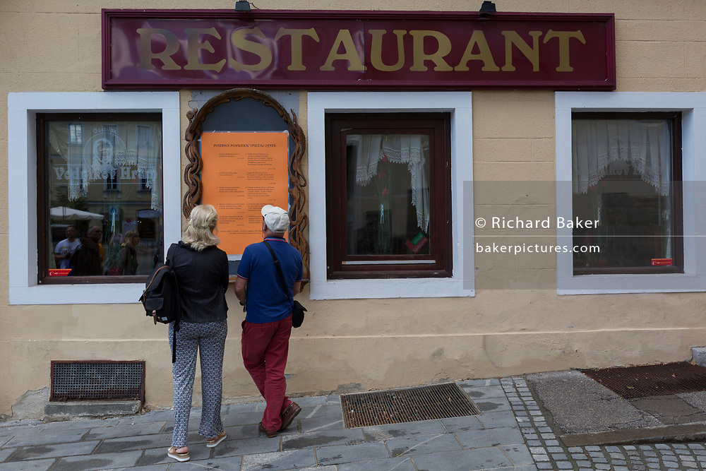 Tourists inspect the menus outside a restaurant in the Slovenian capital, Ljubljana, on 27th June 2018, in Ljubljana, Slovenia.