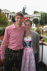 06.10.2013, Kaefers Wiesenschaenke, Muenchen, GER, der FC Bayern Muenchen beim Oktoberfest, im Bild Thomas Mueller of Bayern Muenchen poses with his wife Lisa Mueller in front of the ensemble of the Bavaria statue, a monumental bronze sand-cast 19th-century statue and the Hall of Fame (Ruhmeshalle). The Bavaria is the female personification of the Bavarian homeland and by extension its strength and glory // during the Oktoberfest 2013 beer festival at Kaefers Wiesenschaenke in Munich, Germany on 2013/10/06. EXPA Pictures © 2013, PhotoCredit: EXPA/ Eibner/ Eckhard Eibner<br /> <br /> ***** ATTENTION - OUT OF GER *****