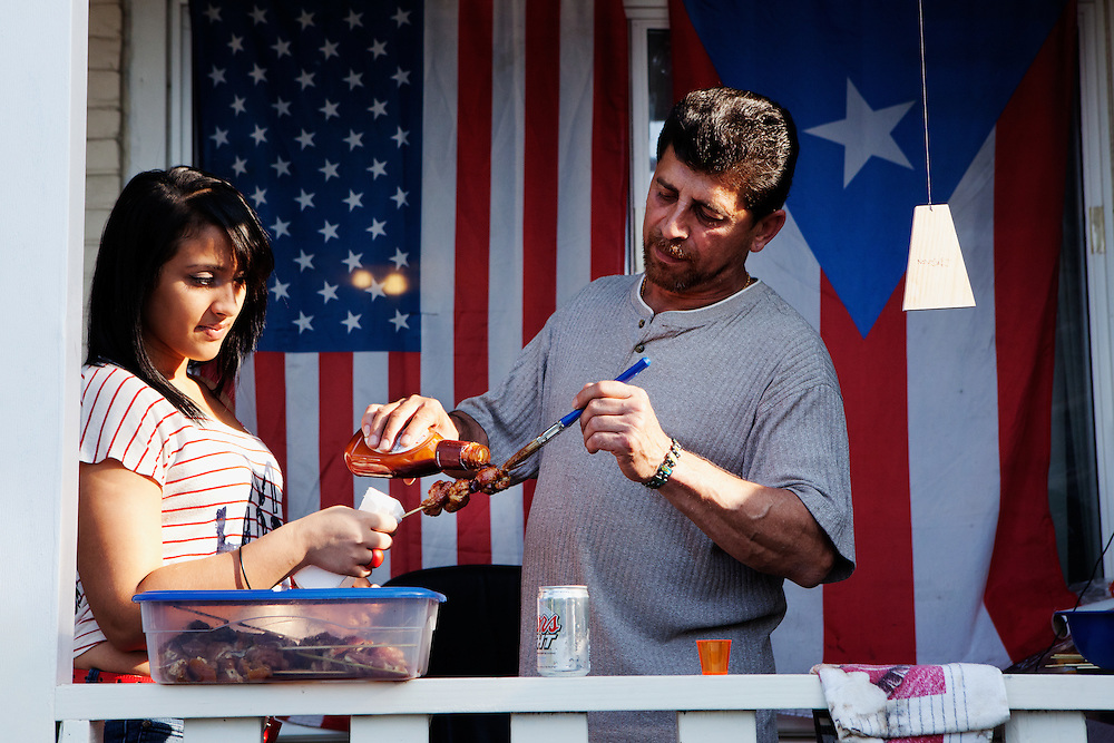 "BETHLEHEM, PA – JUNE 19, 2011: Aeri Rosto (right), 53, grills hot dogs and kabobs to celebrate Father's Day outside the home of Eugenia Rivera, a Hispanic South Side Bethlehem resident. Rosto has lived the U.S. for 32 years. ""My father was a cook,"" he said. ""I started cooking with him when I was eight years old. I love it here. I have my 3 kids, my grandson. It's a great place to live.""<br />