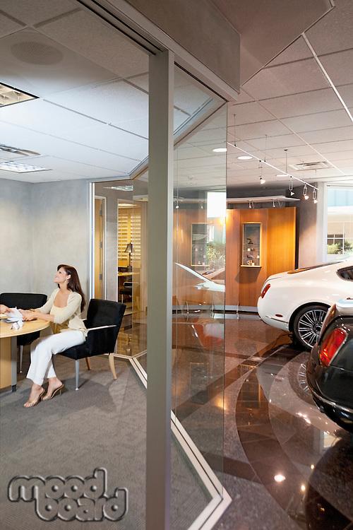 Woman sitting in car showroom office