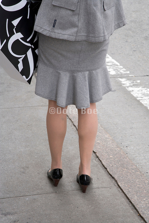 back view of a fashionable dressed woman while standing and waiting for a taxi