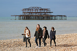 © Licensed to London News Pictures. 25/10/2014. Brighton, UK. A group of Girls take a walk on Brighton Beach, Saturday morning October 25th. A could day with the occasional moments of sunshine. The temperatures are expected to reach 15C in Brighton and the South Coast. Photo credit : Hugo Michiels/LNP