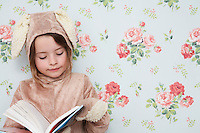 Young girl (5-6) n bunny costume reading book wallpaper with floral pattern in background