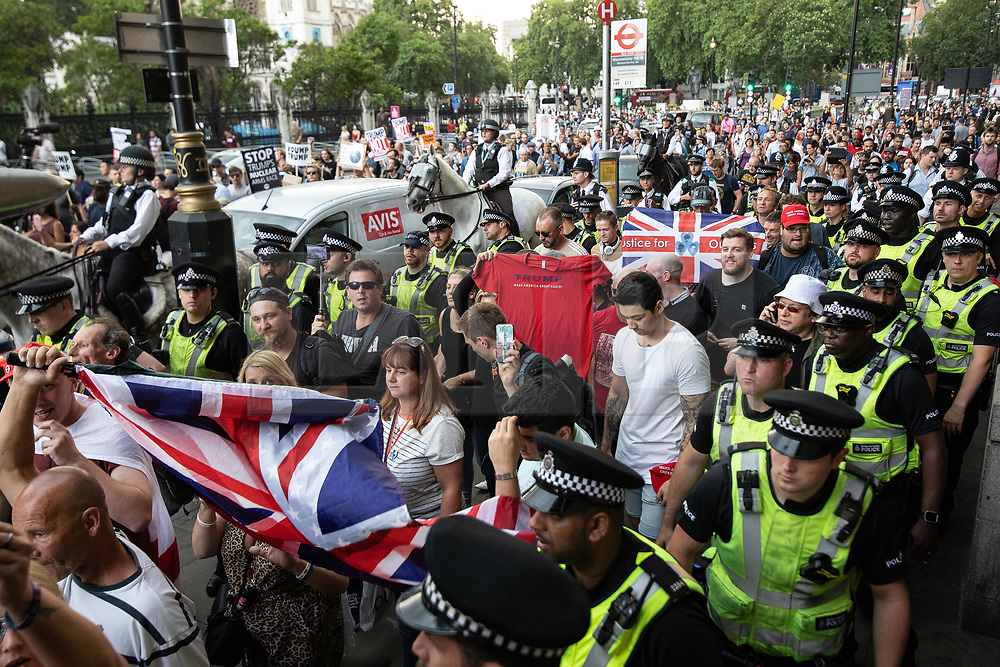 © Licensed to London News Pictures . 13/07/2018. London, UK. A pro-Trump demonstration is lead away by mounted police along Whitehall and to Westminster Station after an anti Trump rally in protest against US President Donald Trump's UK visit . Photo credit: Joel Goodman/LNP