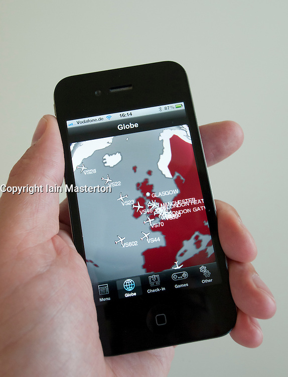 Man using Virgin Airlines flight tracker  app on an iPhone 4G smart phone