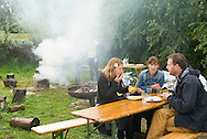 Nederland, Den Bosch, 20140830 <br /> Zelf je eten klaarmaken bij Tussen Kunst &amp; Kitchen. Stevige rookwolken omlijsten het bakken en gaar maken. Mensen aan tafel eten.<br /> Effect Festival - 30 Augustus 2014, De Gemeint 3, bij het Engelermeer tussen Vlijmen en Den Bosch.<br /> eFFect is een manifestatie van lokale duurzame initiatieven die burgers samen van onderop in het leven zetten. Een marktplaats, maar ook workshops door kunstenaars en muziek optredens. Daarnaast ook veel gezonde en alternatieve eettentjes.<br /> <br /> Netherlands, Den Bosch, 20140830.