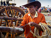 17 FEBRUARY 2018 - BAN LOT, PHETCHABURI, THAILAND: A man repairs an ox cart after a race in Ban Lat, a community about three hours south of Bangkok. The ox cart races are almost 100 years old, and date back to the reign of King Rama V. The races are run on a 100 meter long straightaway course.   PHOTO BY JACK KURTZ