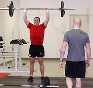 Owner Jason Hoskins of Dayton (right) watches Aaron Pertner of Dayton during a workout of the day session at Vigor Crossfit in Moraine, Wednesday, January 25, 2012.