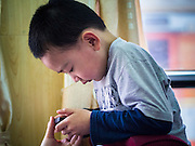 06 APRIL 2012 - HAI PHONG, VIETNAM: A Vietnamese boy plays with a passenger's iPhone on the return leg of the Hanoi to Hai Phong Express. Apple products and Steve Jobs have achieved cult like status in Vietnam and iPhones and iPads are widely available throughout the country. iPhones are sold side by side with Android phones but Vietnamese consumers overwhelmingly prefer the Apple products. The Hanoi to Hai Phong Express Train runs several times a day between Long Bien Station in Hanoi and the Hai Phong Station. Hanoi is the capital of Vietnam and Hai Phong is the 4th largest city in Vietnam. Hai Phong is the principal industrial port in the northern part of Vietnam. It was heavily bombed and mined during the American War (what Americans call the Vietnam War).   PHOTO BY JACK KURTZ