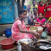 A woman prepares a food to sell outside her house in a slum in Chennai, India. This woman is one of many that Janodayam has helped create self sustaining businesses.
