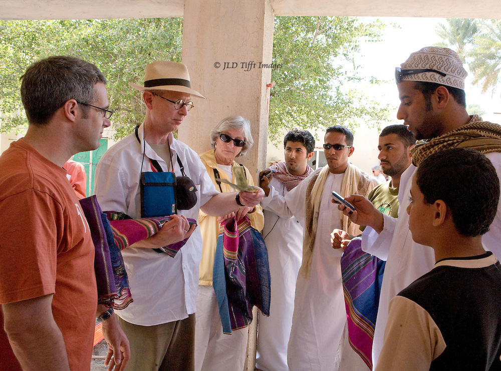 Oman, village of Samad, home of traditional pit weavers. Emmet Brennan buys a piece of fabric from the weavers' representative (sunglasses on his head) as tourists and villagers look on.
