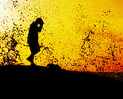 Arts. People. Dancing Man silouette at sunset with golden orange sky as background.  Water splahing up into background..©Patrick King/iAfrika Photos