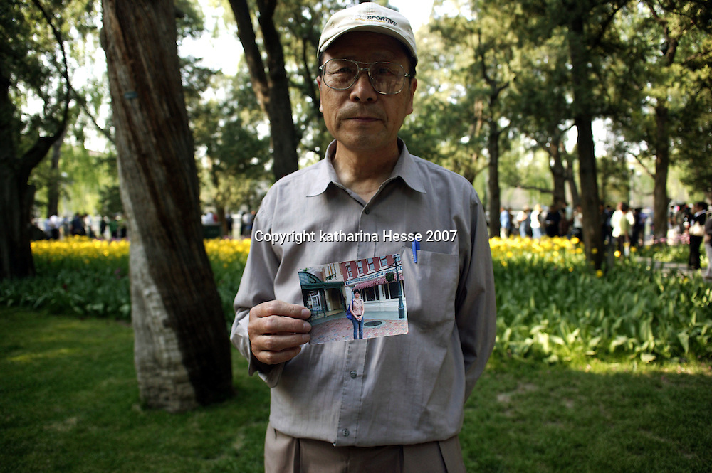 BEIJING, MAY 6: a father shows a description of her daughter in a park, Beijing, May 6,2007. .Twice a week about 800 parents meet in the park trying to find suitable partners for their children. Similar activities are held throughout cities in China ..Due to heavy competition it's difficult for many young Chinese to find partners. This is true especially for women with high education levels like degrees from overseas  and PHDs.   Although customs are changing, there's a lot of pressure on young people to get married.     The children usually don't know of their parent's.activities...