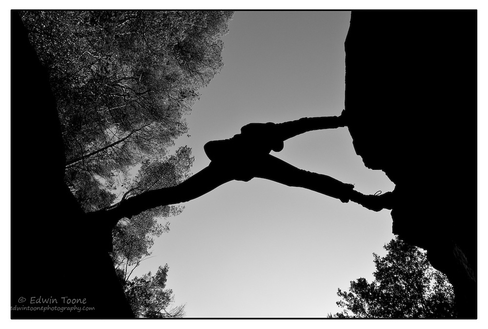 The silhouette o a long legged hiker stretching from one rock to another acoss a creek.