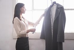 Aug. 31, 2014 - Businesswoman inspecting grey coat (Credit Image: © Image Source/Image Source/ZUMAPRESS.com)