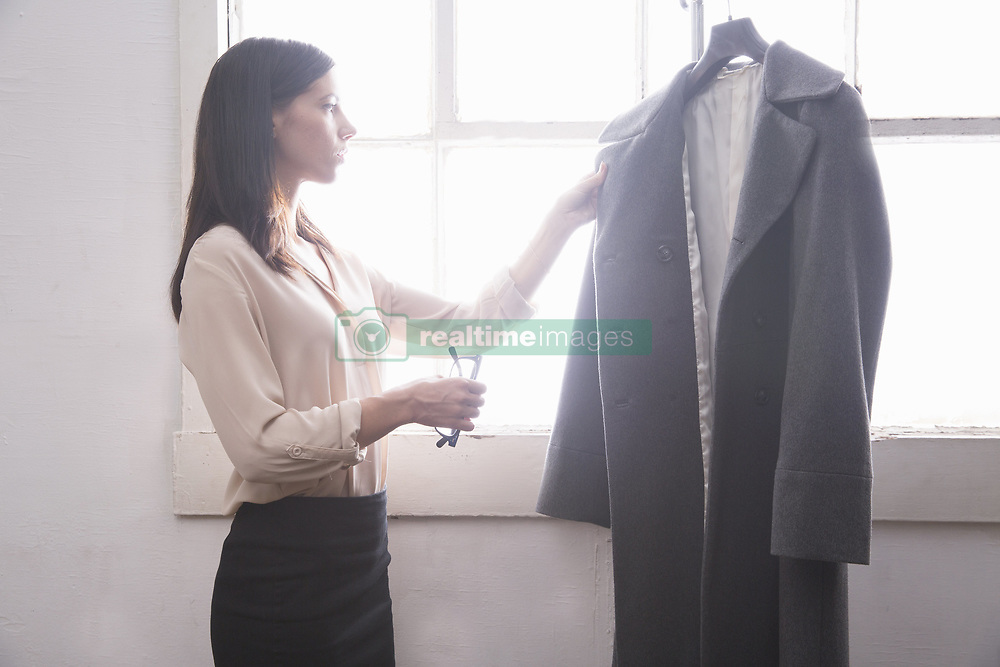 Aug. 31, 2014 - Businesswoman inspecting grey coat (Credit Image: © Image Source/Image Source/ZUMAPRESS.com)