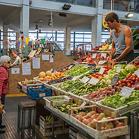 A man serves a customer at the Mercado Coperto (indoor market) in Trieste, Italy.