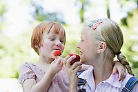 Two girls (3-7) eating fruits smiling