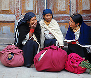 Resting their bright bundles, three women talk and laugh at the Otavalo Market, Ecuador.