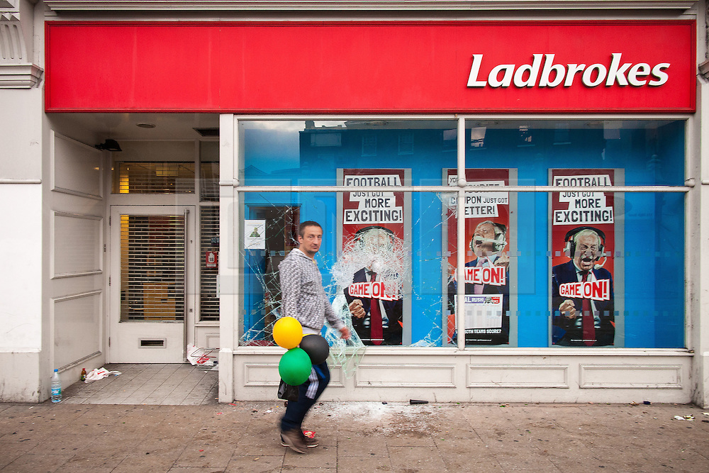 © Licensed to London News Pictures . 07/08/2011 . London , UK . A man walks outside a vandalised branch of Ladbrokes . Overnight rioting and looting in Tottenham , following a protest against the police shooting of Mark Duggan . Photo credit : Joel Goodman/LNP