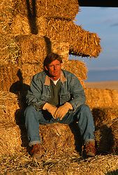 Ranching sitting on hay bales at sunset in New Mexico