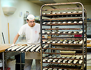 Baker (need name) loads doughy baguettes in preparation for baking at Guglhupf Bakery in Durham, NC.