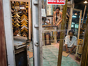 18 APRIL 2015 - BANGKOK, THAILAND:  Workers in a frame shop in the Chatuchak Weekend Market in Bangkok. Chatuchak Weekend Market in Bangkok is reportedly the largest market in Thailand and the world's largest weekend market. Frequently called J.J., it covers more than 35 acres and contains upwards of 5,000 stalls.       PHOTO BY JACK KURTZ