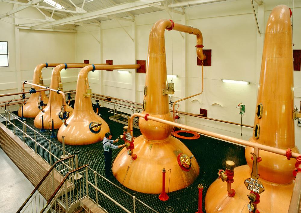 Talisker Whisky distillery, Isle of Skye, Inner Hebrides, Scotland. The still man checks the copper pot stills