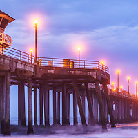 Panorama photo of Huntington Beach Pier and blue morning storm clouds. Known as Surf City USA, Huntington Beach is a popular Orange County Southern California coastal city along the Pacific Ocean in the United States.
