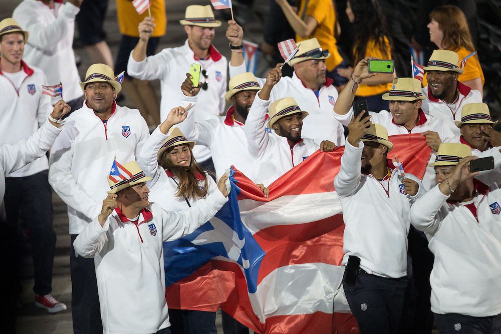 Members of the Puerto Rico team wave to the crowd during the opening ceremonies at the 2015 Pan American Games in Toronto, Canada, July 10,  2015.  AFP PHOTO/GEOFF ROBINS