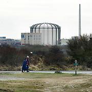 Nederland Petten 7 maart 2009 20090307 Foto: David Rozing ..Kerncentrale Petten, wandelaars in duinlandschap op de voorgrond. Nuclear reactor for the production of medical isotopes to treat cancer. Nucleaire onderzoeksreactor, de snelle flux reactor In Petten wordt onder meer onderzoek gedaan naar manieren om de levensduur van radioactief afval te verkorten. Daarnaast worden er medische isotopen gemaakt, die gebruikt worden voor kankerbestrijding. Hoge Flux Reactor (HFR) op het terrein is onderzoeksreactor en levert ook radioactieve preparaten aan de medische sector t.b.v. diagnostiek en radiotherarpie (bestraling, radiofarmacie); voorheen Reactor Centrum Nederland (RCN) / Kerncentrale Petten..Foto: David Rozing/