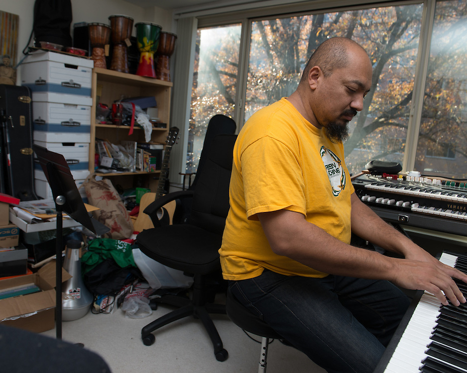 December 5, 2015 - Fairfax, VA - A day in the life of &quot;Doc Nix,&quot; aka Dr. Michael Nickens, the Director of the Athletic Bands for George Mason University. Here, he plays a keyboard in his apartment filled with musical instruments.<br /> <br /> Photo by Susana Raab