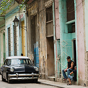 Two men sitting in the doorway of a house in Havana with a vintage American car