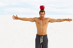 shirtless man balancing a very large fake apple on his head in the desert