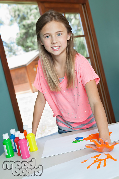 Portrait of a young girl making orange hand print on table