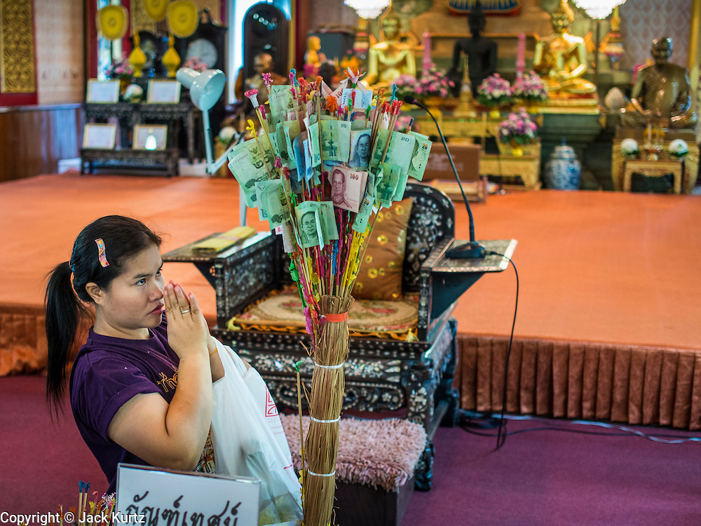 "13 MAY 2013 - BANGKOK, THAILAND: A woman prays after making an offering during Vesak ceremonies at Wat That Thong in Bangkok. Vesak, called Wisakha Bucha in Thailand, is one of the most important Buddhist holy days celebrated in Thailand. Sometimes called ""Buddha's Birthday"", it actually marks the birth, enlightenment (nirvana), and death (Parinirvana) of Gautama Buddha in the Theravada or southern tradition. It is also celebrated in Cambodia, Laos, Myanmar, Sri Lanka and other countries where Theravada Buddhism is the dominant form of Buddhism.     PHOTO BY JACK KURTZ"