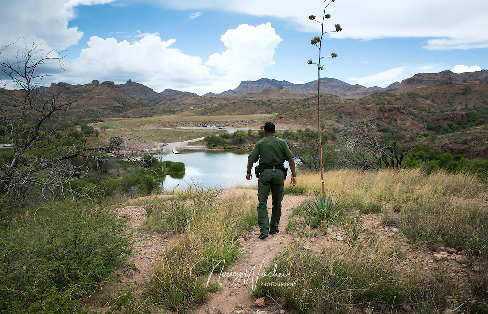 Border Patrol Agent Bryan Flowers walks above Pe&ntilde;a Blanca Lake, a small recreation area about 17 miles northwest of Nogales, Ariz., July 16. Because of the water availability, smuggling routes through here are common, Flowers said. Photo taken July 16, 2014.<br /> NANCY WIECHEC