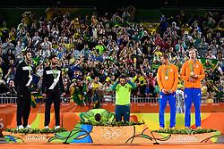 18.08.2016, Rio de Janeiro, Copacabana<br /> Beachvolleyball, Olympische Spiele, Siegerehrung<br /> <br /> Podium mit Medaillengewinnern - Alison Cerutti (#1 BRA) kuesst Podium<br /> <br /> Foto: Conny Kurth / www.kurth-media.de