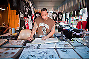 July 25 - PHOENIX, AZ: ROBERT LARIOS, a vendor in El Gran Mercado, looks over some of his designs in his stall. He said his business is down more than 60% this year and he attributes most of the decline to Arizona's anti-immigrant laws that are driving his customers away. El Gran Mercado (The Big Market) in Phoenix is the largest flea market in the Phoenix area and has served the area's immigrant community for more than 20 years. With more than 150 small independent stalls selling Mexican clothes, cowboy hats, Mariachi music and food stalls selling Mexican favorites like birria chivo (goat stew) and menudo (tripe) it was more like a Mexican market than an American mall. Business in the mercado is down more than half this year because many immigrant families, legal and illegal, are leaving Arizona before the state's tough new anti-immigrant law, SB 1070 goes into effect on July 29. SB 1070 allows local police officers to check the immigration status of people they have probable cause to believe may be in the US illegally and requires immigrants to carry their immigration papers with them at all times.    Photo by Jack Kurtz