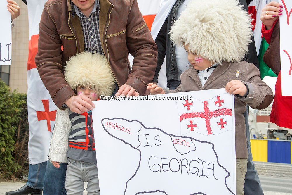 Brussels 20130419 A small group of people from Georgia demonstrate in front of the European Commission. They state to be for Europa and against influence of Russia. Small boys wear the traditional Georgian fur hats called Chokha,part of their proud cultural heritage.