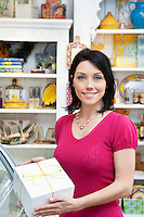 Portrait of a beautiful mid adult customer holding box in cake shop