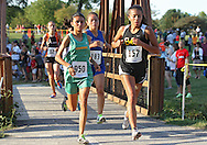 Kennedy's Katie Wampole (950), Washington's Shannon Gorman (183), and Bettendorf's Mahnee Watts (157) cross the bridge during the Cedar Rapids Invitational at Noelridge Park in Cedar Rapids on Thursday, September 6, 2012. Gorman placed third with a time of 14:54.88, Wampole placed eleventh with a time of 15:26.31, and Watts placed fiftieth with a time of 15:35.80.