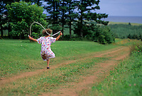 Girl, 6, skips rope as she goes along red dirt road, PEI