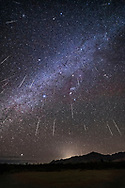 A composite of the 2017 Geminid meteor shower, from the peak night of December 13, with the radiant in Gemini, at top, high overhead. So meteors appear to be raining down to the horizon. This was certainly the visual impression.<br /> <br /> At least one meteor, at left, is not a Geminid, as it does not point back to the radiant. <br /> <br /> The Milky Way runs diagonally across the frame, from Puppis at lower left, to Auriga at upper right. Orion is at centre. Gemini is at top. <br /> <br /> This is a stack of 24 images, some with 2 or 3 meteors per frame, each a 30-second exposure at f/2.5 with the Rokinon 14mm SP lens and Canon 6D MkII at ISO 6400. The images are the 24 frames with meteors out of 171 taken over 94 minutes from 2:05 am to 3:39 am MST. <br /> <br /> The ground is a stack of 8 images, mean combined to smooth noise. The background base-image sky is from one exposure. <br /> <br /> The camera was on a fixed tripod, not tracking the sky. I rotated and moved each image in relation to a base image in order to place each meteor at approximately the correct position in relation to the background stars, to preserve the effect of the meteors streaking from the radiant near Castor at top of the frame. <br /> <br /> Taken from Quailway Cottage, near the Arizona Sky Village in southeast Arizona, with a view looking southwest toward the Chiricahua Mountains. From this latitude, Canopus appears low above the southern horizon at left.