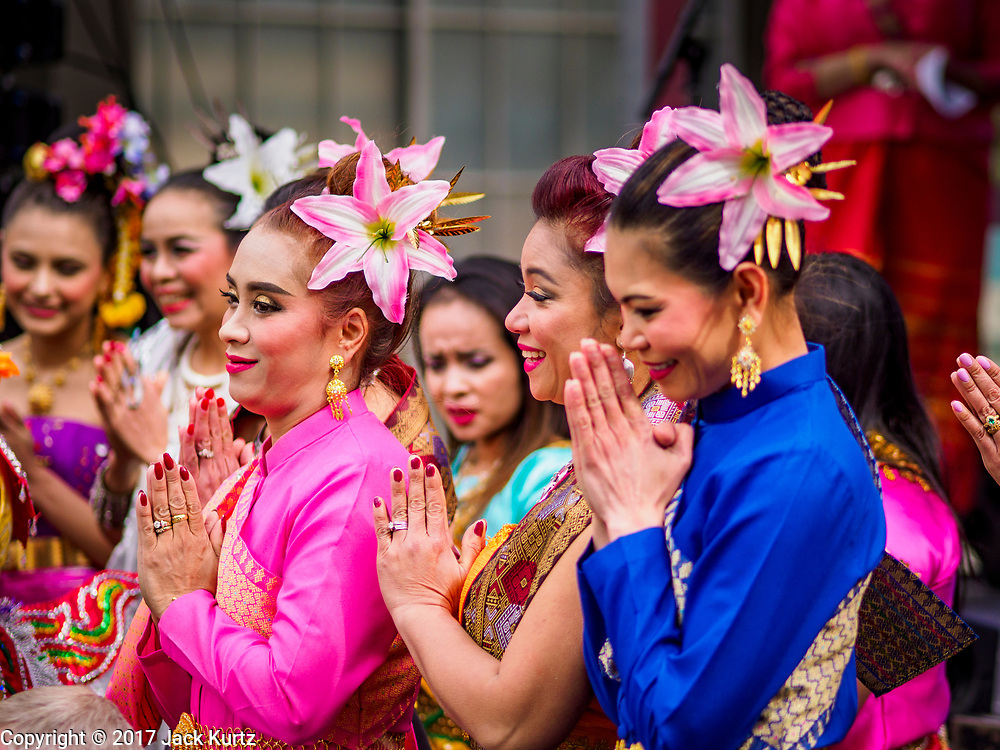 """29 APRIL 2017 - MINNEAPOLIS, MINNESOTA: Thai women """"wai"""" (a traditional Thai greeting) during New Year greetings at Songkran Uptown in Minneapolis. Several thousand people attended Songkran Uptown on Hennepin Ave in Minneapolis for the city's first celebration of Songkran, the traditional Thai New Year. Events included a Thai parade, a performance of the Ramakien (the Thai version of the Indian Ramayana), a """"Ladyboy"""" (drag queen) show, and Thai street food.     PHOTO BY JACK KURTZ"""